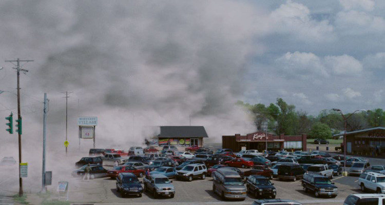 A parking lot showing a wall of mist blowing over the cars.
